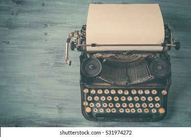 Old black typewriter with paper worth on the painted table