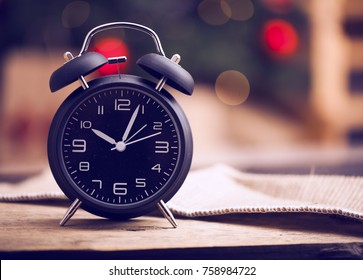 Old Black vintage alarm clock on wooden table on blur background of Christmas tree. New Year Theme