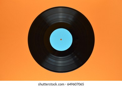 old black vinyl record with blank cyan label centered on orange background