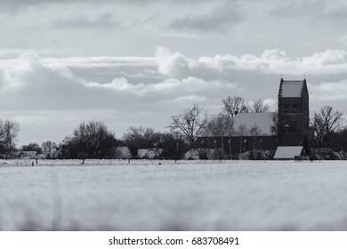 Old black and white photo of dutch village with church tower in snow. Geesteren. Achterhoek. Gelderland. The Netherlands.