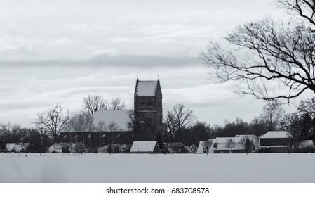Old black and white photo of old dutch village with church tower in snow. Geesteren. Achterhoek. Gelderland. The Netherlands.