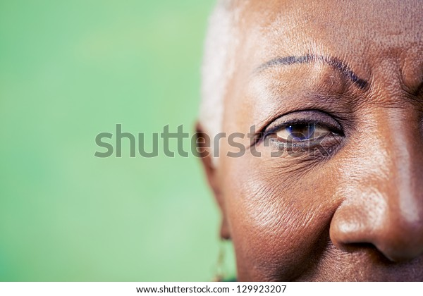 Old black woman portrait, close-up of eye and face on green background. Copy space