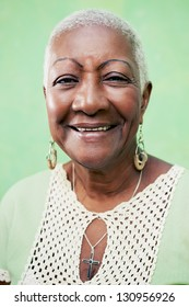 Old black woman portrait, lady in elegant clothes smiling on green background