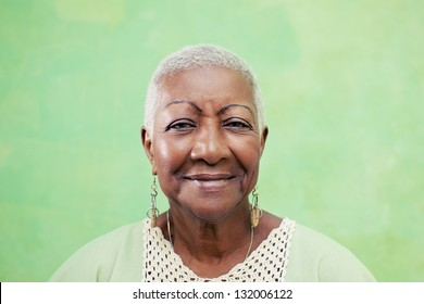 Old black woman portrait, lady in elegant clothes smiling on green background. Copy space