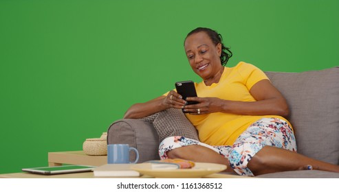 Old black woman using mobile phone while sitting on couch on green screen