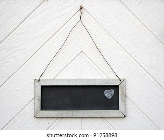 Old blackboard sign with a chalk heart drawn on it, hanging on a wooden wall or door
