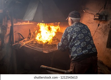 Old blacksmith burning coal. Blacksmith setting fire for molting metal to be forged with hammer on the anvil.