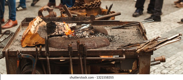Old blacksmith tools on the medieval fair. Anvil, hammer, fire, chain. Brazier on city the street forge workshop. Forge fire at summer medieval fair