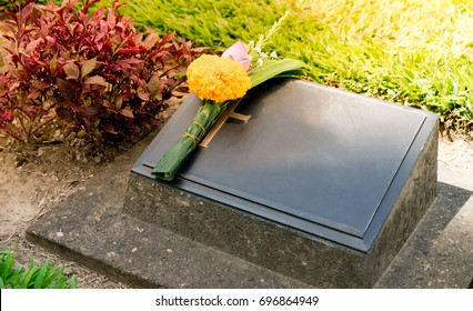 Old blank cemetery stone or tombstone and graves in dark area with Thai flower. Gravestone with blank space for text. Blank cemetery concept.