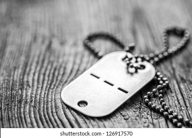Old blank dog tag on wooden background. Very shallow depth of field with focus on the lower part of a tag