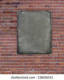 Old blank metal plate on red brick wall background