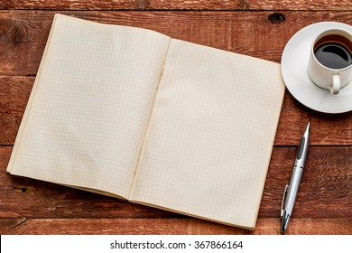 old blank notebook opened on a  red barn wood table with a cup of coffee