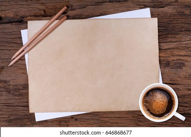 Old blank paper and a cup of coffee on wooden