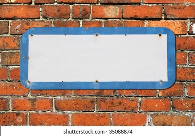 Old blank sign on a red brick wall.