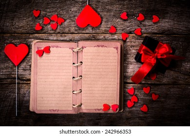 Old blank small book with the hearts on wooden background
