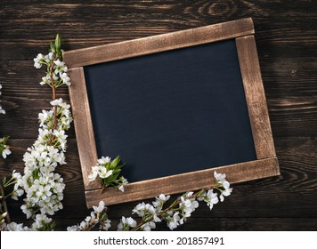 Old blank vintage school slate or chalkboard lying on an old rustic wooden background with dainty white flowers in two corners ready for your text or message