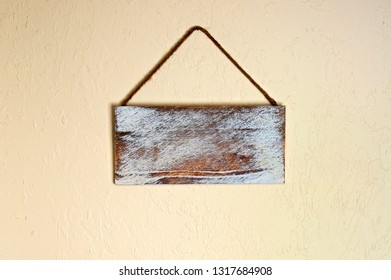 An old blank wooden sign hanging on a wall indoors. with copyspace.