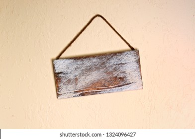 An old blank wooden sign hanging crooked on a wall indoors. with copyspace.