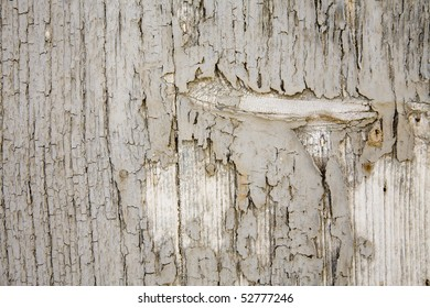 Old blistered grey paint on a wooden panel