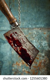 Old bloody meat cleaver hanging on the chain. Horror concept