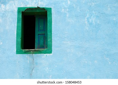 Old blue adobe wall with a window. Architecture background.