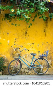 Old blue bicycle parked on street with grunge yellow wall .Selective focus.