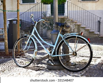 Old blue bicycle parked at post
