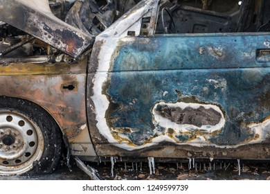 Old blue car after fire. Arson car for the sake of insurance. Rusty burnt metal close up. Burnt texture. Full car accident insurance.