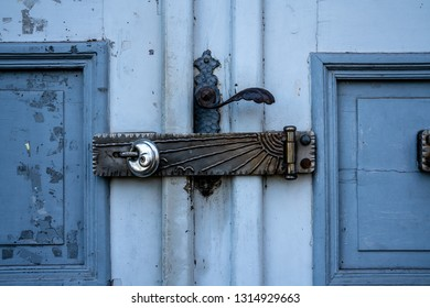An old blue door with flaking paint and a closing hatch with a padlock