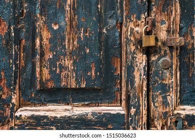 Old blue door with peeled wood, a padlock and a lock in Venice, Italy