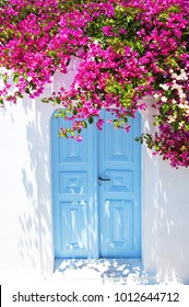 Old blue door and pink flowers, traditional Greek architecture, Santorini island, Greece. Beautiful details of the island of Santorini, white houses, blue doors and shutters, the Aegean Sea.
