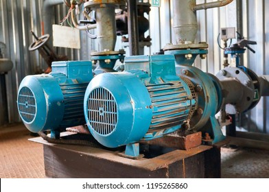 Old blue electric motor to the pump, valve and pressure gauge on the pipeline. Industrial background.