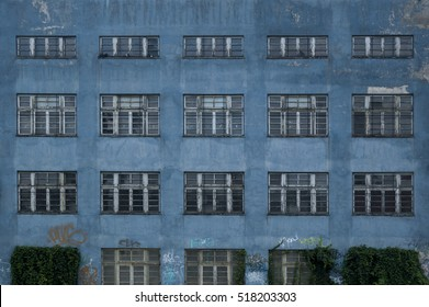 Old blue industrial building facade with fenced fragmented windows in row