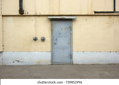 Old blue iron door with a yellow white wall. Abstract blank horizontal background of a stained steel door with traces of corrosion and walls with smudges, age-damaged plaster, dark wires.