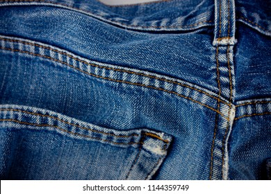 old blue jeans seam detail cloth of denim for pattern and classic background close up