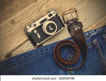 old blue jeans, vintage leather belt and ancient rangefinder camera. still life in a nostalgic manner. instagram image filter retro style