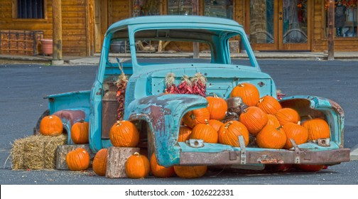 An old blue pickup trick with missing doors, wheels and engine sits on a street and is filled with pumpkins and red chili ristras - decoration for the harvest season.