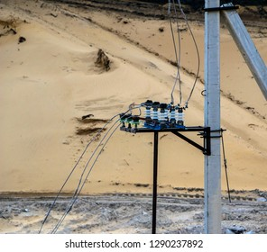 An old blue rusty transformer supplies electricity through the traverse, wires and electric supports in a sand quarry.