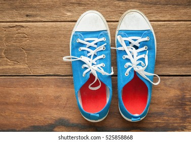 Old Blue shoes on a wooden background with copy space.