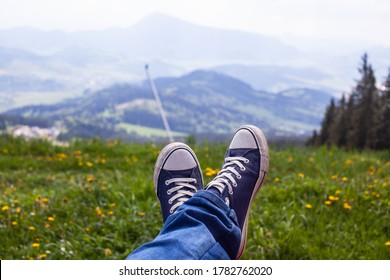 Old blue sneakers on the legs of a young guy with a beautiful mountain view in the background.