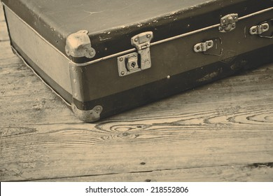 Old blue suitcase on the wooden vintage floor
