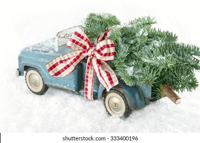 Old blue toy truck carrying a green Christmas tree covered with snow and a red ribbon on white snowy background
