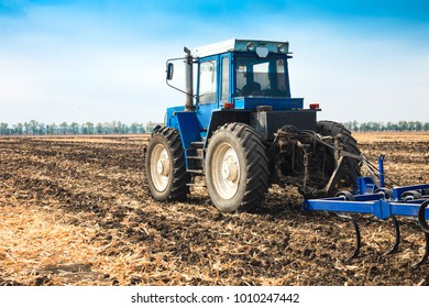 Old blue tractor with a plow in a field on a sunny day. The concept of work in a fields and agriculture industry.
