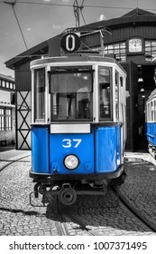 old blue tram on black and white background