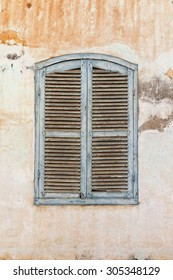 An old, blue window on an old house