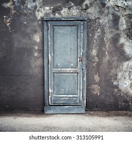 Old blue wooden door in dark concrete wall, empty abstract interior, square background texture