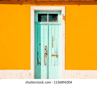 The old blue wooden door of the home that houses the orange house wall.