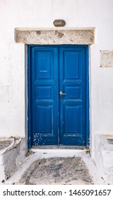 Old blue wooden door of traditional white house in Amorgos, Greece.