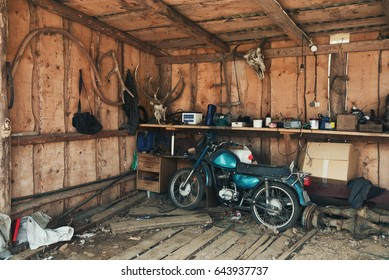 Old Blue-Green Motorbike In Picturesque Barn.Vintage Motorcycle In Old Hangar Against A Wall With Deer Antlers, A Bison Head And Many Interesting Rare Objects. Old Shed With Old Moped And Wooden Walls