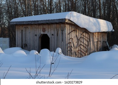 An Old Board And Batten Shed With Antiques Hanging On It Covered In Snow